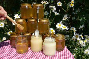 Our three textures of honey with jars of runny honey as background